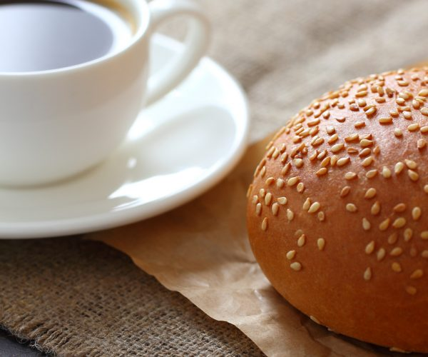 A sesame bun and a mug of coffee on kraft paper and burlap tablecloth.